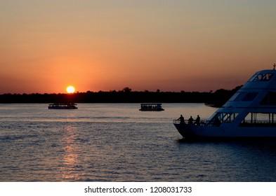 Livingstone, Zambia, Africa. June 2018. Tourists enjoying the sunset over the Zambezi River near Livingstone.