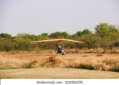 LIVINGSTONE, ZAMBIA - CIRCA NOVEMBER 2017: A microlight taking tourists over the Victoria Falls, a waterfall in southern Africa on the Zambezi River at the border between Zambia and Zimbabwe.