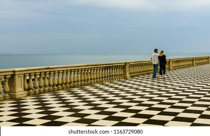 Livorno, Italy - 2018. Young couple going for a walk at Terrazza Mascagni, in Livorno, Italy. It is an elegant waterfront terrace with a gazebo & benches offering panoramic sea and sunset views.