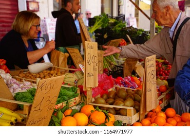 LIVORNO, ITALY - APR 23, 2018 - Woman buying fresh vegetables in the market of Livorno, Italy