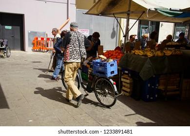 LIVORNO, ITALY - APR 23, 2018 - Bicycle rider in the market of Livorno, Italy