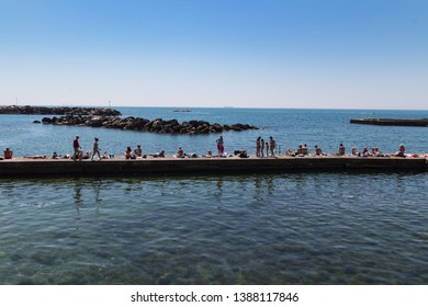 LIVORNO, ITALY - APRIL 22, 2018 - Beautiful Livorno urban sea: people sunbathing and relaxing