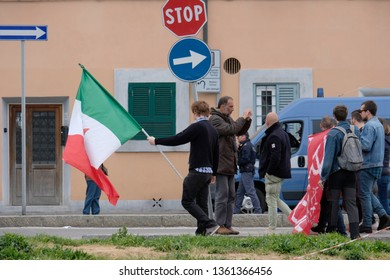 LIVORNO, ITALY - APRIL 6, 2019: A man with an Italian flag marching ahead of a protest for the Italian communist party in the city of Livorno. A bystander in the background is taking pictures.