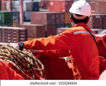 LIVORNO, Italy - August, 13, 2019 - Asian seaman at forward mooring station wit heaving line in hand.