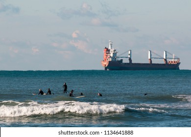 Livorno, Italy - july 2015: surfers waiting for waves, container ship in background