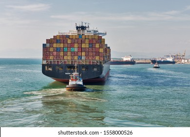 LIVORNO, ITALY - JULY 23, 2019: Tugs and huge cargo container ship Maersk Kowloon entering port. Maersk Line is a world largest Danish international container shipping company. It was founded in 1928.