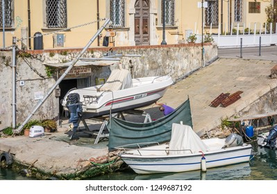 LIVORNO, Tuscany, Italy - April 28, 2018: Man restoring vintage wooden rowing boat in the Venice quarter of Livorno, Tuscany, Italy.