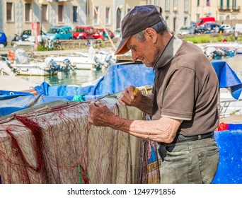 LIVORNO, Tuscany, Italy - april 28, 2018: old fisherman repairing the net for fishing on an area that many call little Venice, city of Livorno in Tuscany, Italy.
