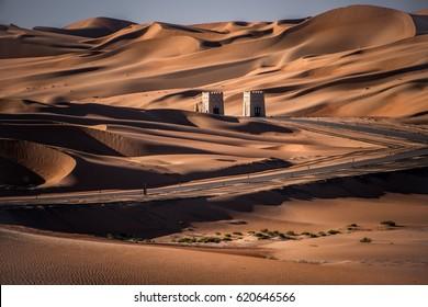 Liwa, Abu Dhabi, UAE-February 2, 2016: A view of Liwa desert and road along the Empty Quarter before sunset in Abu Dhabi, United Arab Emirates on February 2, 2016