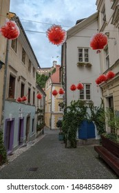 Ljubjana, Slovenia - August 21 2019: decorations on the narrow street named Jewish street in old part of city with a view towards Ljubljana castle.