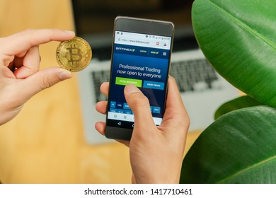 Ljubljana, Slovenia 29.4.2019: Businessman holding mobile smartphone with opened Bitfinex website and Bitcoin coin on a office desk