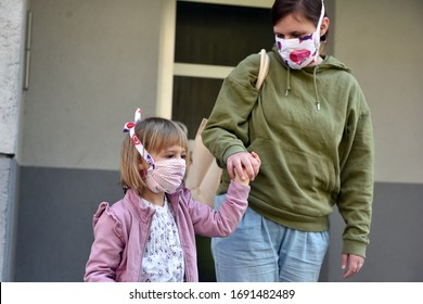 Ljubljana / Slovenia - 4/1/2020: Daughter and mom wearing a DIY face masks for protection against coronavirus, walking in the street.