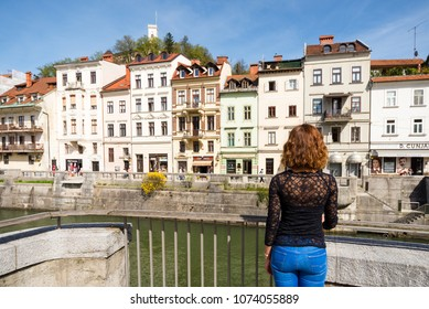 Ljubljana / Slovenia - April 14 2018: Young woman is admiring old buildings and apartments in old part of Ljubljana, Slovenia