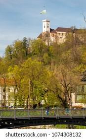 Ljubljana / Slovenia - April 14 2018: Young woman is looking at the Ljubljana castle from a bridge in Ljubljana, Slovenia