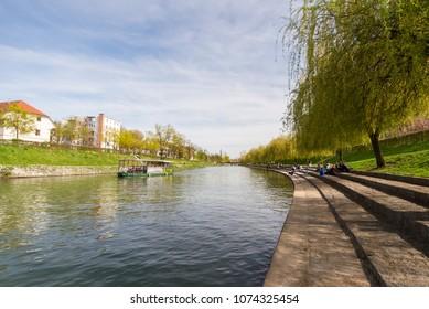 Ljubljana / Slovenia - April 14 2018: Trnovo beach and riverbanks of Ljubljanica river with tourist boat on the river in Ljubljana, Slovenia.