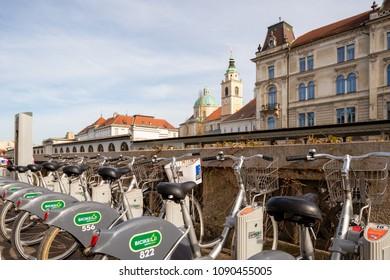 Ljubljana / Slovenia - April 14 2018: Rent a bikes with Plecnik architecture and Ljubljana cathedral in the background in old part of Ljubljana, Slovenia.