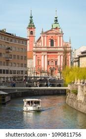 Ljubljana / Slovenia - April 14 2018: Tourist boat is taking tourists on a cruise on Ljubljanica river in Ljubljana, Slovenia