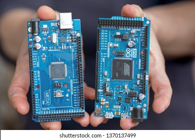 Ljubljana, Slovenia - April 15 2019:  Hands offering us to choose betwen the Arduino Due and Arduino Mega microcontroller board, both very popular in education and makers space .