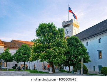 Ljubljana, Slovenia - April 27, 2018: Courtyard with tourists and Old castle tower with Slovenian flag in the hill of Ljubljana, Slovenia