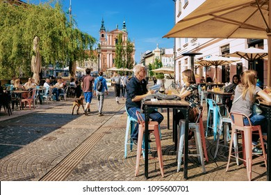 Ljubljana, Slovenia - April 27, 2018: People at sidewalk street cafe near Franciscan Church of the Annunciation in the historical center of Ljubljana, Slovenia