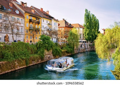 Ljubljana, Slovenia - April 27, 2018: Excursion boat in Ljubljanica River in the historical center of Ljubljana, Slovenia
