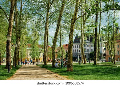 Ljubljana, Slovenia - April 28, 2018: People in the park at Congress Square in the historical center of Ljubljana, Slovenia. University of Ljubljana on the background
