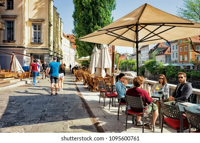Ljubljana, Slovenia - April 29, 2018: People at sidewalk cafe at the embankment of Ljubljanica River in the historical center of Ljubljana, Slovenia