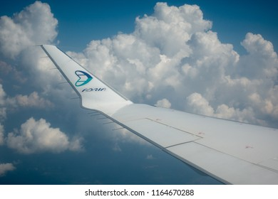 Ljubljana, Slovenia - August 25 2018: View through airplane window on wing of airplane, Adria Airways logo on wing tip, clouds and blue sky background