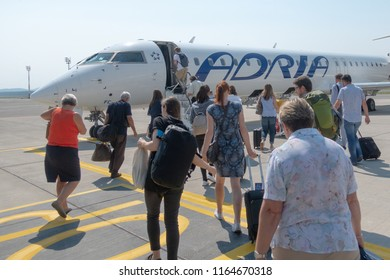 Ljubljana, Slovenia - August 25 2018: Passengers board Adria Airways Bombardier CRJ-900 passenger jet at Ljubljana Airport to SKopje. Adria is local carrier connecting short flights to the Balkans.