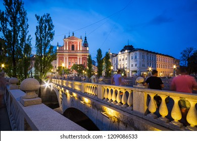 LJUBLJANA, SLOVENIA - CIRCA AUGUST 2018: View of Franciscan Church of the Annunciation right behind the famous three bridges during blue hour
