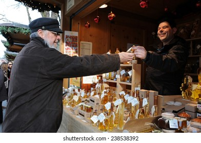 LJUBLJANA, SLOVENIA - DEC. 13, 2014: Customer chose a small bottle of honey brandy at kiosk at Christmas and New Year's market in open air on the street at pedestrian zone.