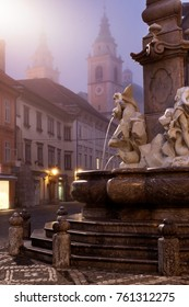 Ljubljana, Slovenia: famous Robba Fountain seen at dusk, with the cathedral's towers on background.