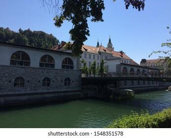 Ljubljana / Slovenia - July 10, 2016: View to river Ljubljanica, Central Market's colonnade and Butcher's bridge in Ljubljana capital of Slovenia. Beautiful city center of Ljubljana at sunny day.