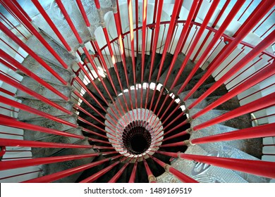 Ljubljana / Slovenia - July 27 2019: View down the steel double helix spiral staircase at the Ljubljana Castle tower with red bar posts and ornate steps