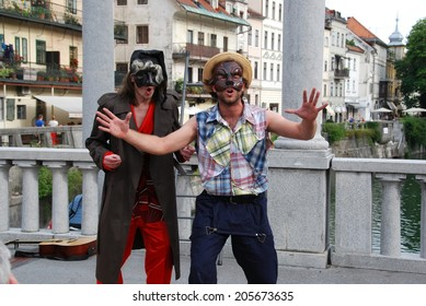 LJUBLJANA, SLOVENIA - JULY 4, 2014: Lovro Finzgar and Nik Skrlec (SI) as Scapino and Pantalone (from Italian commedia dell' arte) in show Masked Criminal at traditional street theater Ana Desetnica.