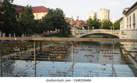 Ljubljana / Slovenia - July 8, 2016: Colorful love locks at Butcher's Bridge in central Ljubljana, Slovenia. Dragon Bridge in the background.