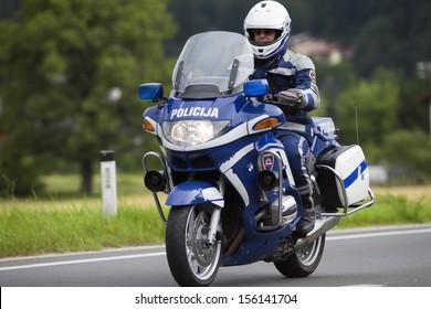 LJUBLJANA, SLOVENIA - JUNE 10: Member of Slovenian police force on bike halts the traffic in view of annual bicycle marathon on June 10, 2012 in Ljubljana, Slovenia.