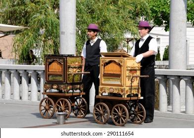 LJUBLJANA, SLOVENIA - JUNE 13, 2015: Slovenian Barrel organ players try to evoke nostalgic atmosphere on Cobblers bridge in old city center