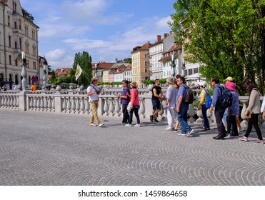 Ljubljana, Slovenia, June 18, 2019.  Tour guide with a flag leading a group of asian tourist through the old part of Ljubljana