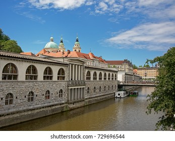 LJUBLJANA, SLOVENIA, JUNE 2, 2017,neoclassical central market building, designed by Jose Plecnik, view from across river Ljubljanica, with towers of the cathedral in the back. Ljubljana, 2 June 2017