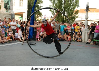 LJUBLJANA, SLOVENIA - JUNE 28: Croatian circus group Kam Hram with performance Look At The Sky at traditional street theater Ana Desetnica on June 29, 2012 in Ljubljana, Slovenia. Spin with one leg.