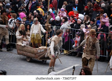 LJUBLJANA, SLOVENIA - MARCH 5: Lake dwellers, our ancestors from neolithic, with their home made fishing boat (originally made from a trunk).Carnival parade in Ljubljana, Slovenia, 5th of March 2011.