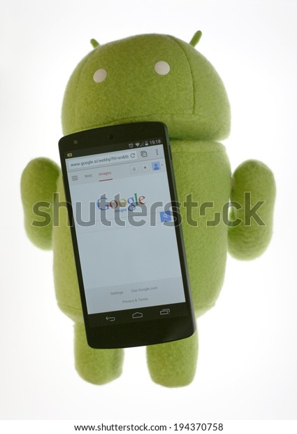 LJUBLJANA, SLOVENIA - MAY 21, 2014: Google Nexus 5 LG smartphone with Android robot figure plush toy. The Nexus 5 is the first device to feature version 4.4 of Android operating system.