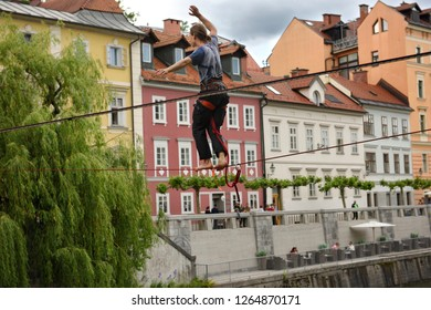 Ljubljana, Slovenia - May 21, 2017: Young man balancing on a slack line high over the Ljubljanica river canal in the old section of Ljubljana Slovenia Europe