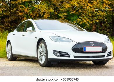LJUBLJANA, SLOVENIA - October 21, 2016: White Tesla car Model S parked in autumnal european forest