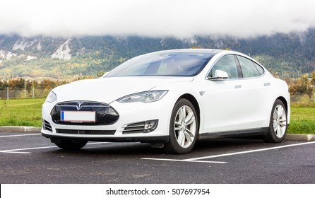 LJUBLJANA, SLOVENIA - October 21, 2016: White Tesla car Model S standing near Alps. Clouds on the mountain