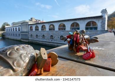 LJUBLJANA, SLOVENIA - OCTOBER 24 - The bronze sculptures of the Slovenian sculptor Jakov Brdar on the Butcher bridge across the Ljubljanica River are decorated with locks of lovers. Plecnik's Arcade,