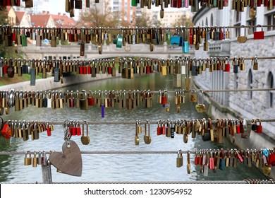 Ljubljana, Slovenia - October 28, 2017: Colorful love locks at Butcher's Bridge in central Ljubljana, Slovenia. Dragon Bridge in the background. Selective focus.
