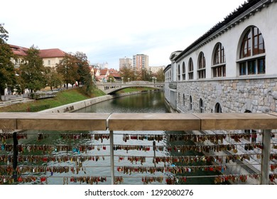 Ljubljana, Slovenia - October 28, 2017: Visitors at Butcher`s Bridge in central Ljubljana, Slovenia. Butcher`s Bridge is famous for its abstract sculpture and love lockets.