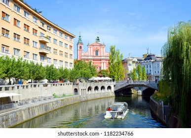 LJUBLJANA, SLOVENIA - September 08, 2018 : Franciscan Church of the Annunciation and river Ljubljanica with excursion boat in city of Ljubljana.